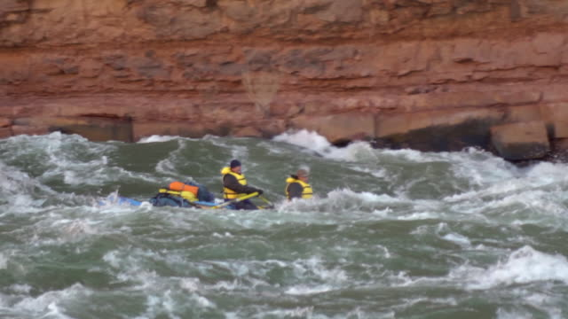WS SLO MO PAN Females in red raft moving down rapid and red cliff in background / Grand Canyon, Arizona, USA