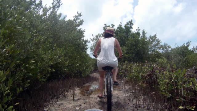Females rides through beach path