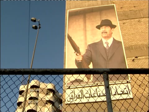 A fence surrounds a building where a mural of Saddam Hussein hangs.