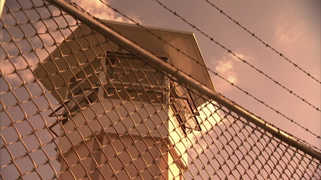 Fence topped w/ barbed wire w/prison guard watch tower w/ windows open BG No people Correctional facility incarceration secured security not jail