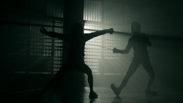 Fencers on back lit