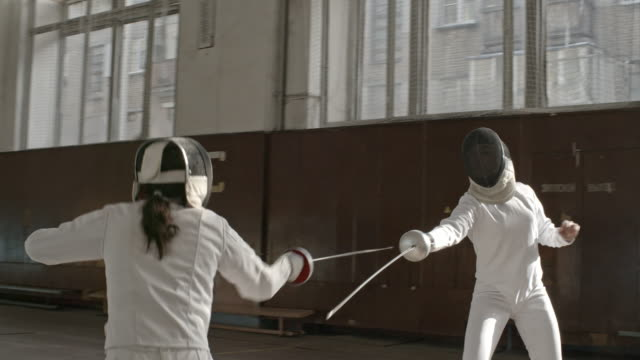 Fencers practicing in large gym