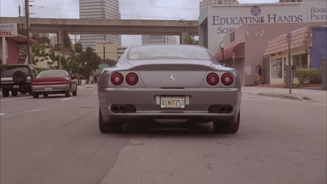 A Ferrari 575m Maranello takes off down a street, suddenly brakes, and turns 180 degrees in front of several muscle cars.