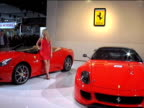 WS Ferrari California and Ferrari 599XX beautiful blonde in slinky red dress walks over to California and poses for pictures next to it / WS LA front...
