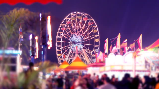 Ferris Wheel, Carnival Rides and Games at Night