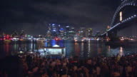 A ferry approaches Sydney Harbour Bridge in front of a New Year's crowd at night.