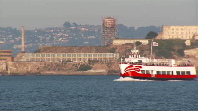Ferry boat w/ unidentifiable passengers moving across San Francisco Bay Alcatraz Island w/ water tower amp lighthouse BG Transportation tourist...