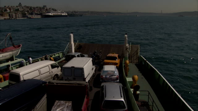 A ferry carries cars through a harbour.