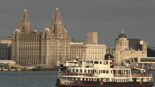 Ferry passing by Pier Head in Liverpool showing the Royal Liver Building Cunard Building and Port of Liverpool Building known as 'The Three Graces'