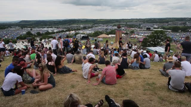 Festival goers take in the view at the Glastonbury Festival at Worthy Farm Pilton on June 24 2015 in Glastonbury England