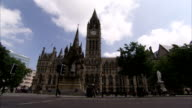 A few pedestrians pass the Manchester Town Hall in England. Available in HD.