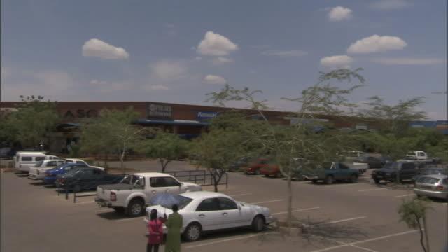 Few unidentifiable Batswana walking through parking lot full of cars unidentified shopping center BG trees around