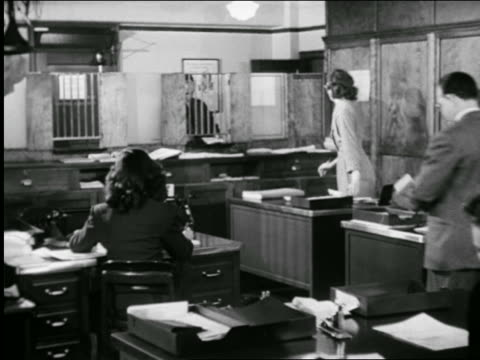 B/W 1947 PAN office workers at desks behind bars in insurance office / industrial