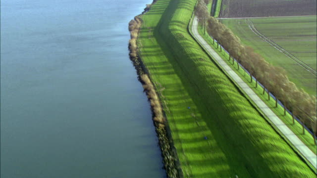 LOW AERIAL, Fields and town along grass covered sea wall, Netherlands