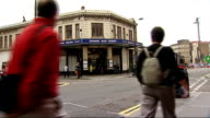 Relatives hold ceremony Edgware Road Station Commuters on CCTV screen / Edgware Road Station sign over entrance PULL back to wide shot of station and...
