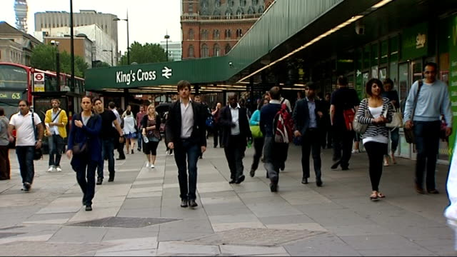 Relatives hold ceremony ENGLAND London King's Cross Station EXT Panning shot of commuters along outside King's Cross station / People giving out free...
