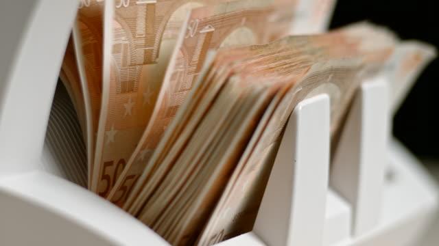 SLO MO LD Fifty euro banknotes shuffling through a money counter and onto a stacker