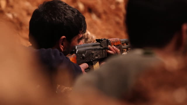 Fighters from the Free Syria Army aiming with AK47 rifles while surrounded by road side explosives and booby traps