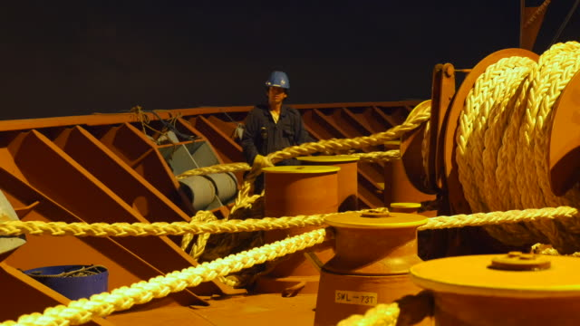 A Filipino sailor manages and winches the heavy ropes of a container ship from the bow as it prepares to leave port