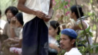 Filipino villagers stand around or sit and do nothing, as if they are being detained.