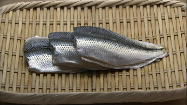 Filleted Kohada lie on a bamboo tray.