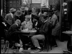 1916 B&W Film montage MS man putting card between toes to pass under table during poker game/ man taking card and looking around