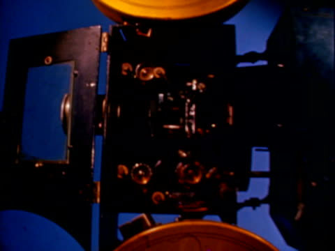 Film projector shot in stop motion projector with parts moving in stop motion animation / inside projector as film is threaded in stop motion...