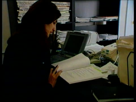 Film reviews/Oscar previews ITN Woman scriptwriter looking thru script CS Pile of scripts TILT Advertising sign for '10 Things I Hate About You'