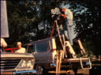 / WS film set for a 1964 Studebaker commercial film camera is on tripod in the back of a Studebaker Wagonaire / WS angle on film camera and cameraman...
