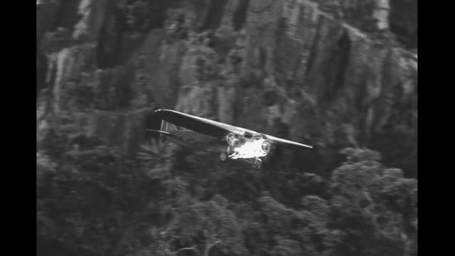 Film set miniature mountains and forest camera assistant adjust model plane with flaming propeller and scrambles out of the way / plane moves over...