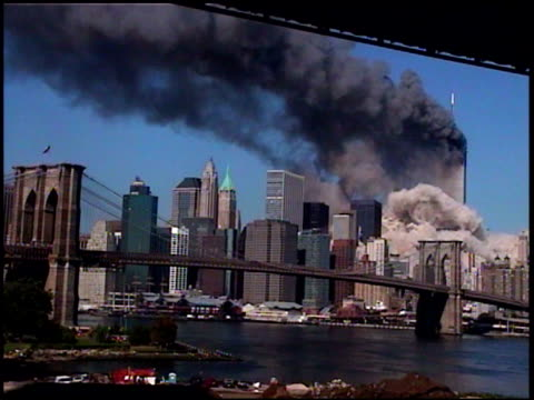 Filmed from Brooklyn shot of towers burning black smoke with Brooklyn Bridge and boat moving under it / shot of towers burning black smoke and first...