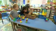 Final day to claim free childcare / nurseries have financial fears INT Child and nursery worker at nursery Building blocks on table