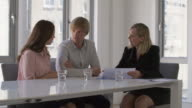 MS A financial adviser talks with clients in an office