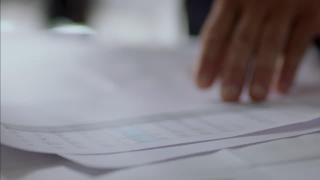 Financial advisor digs through paperwork in business meeting