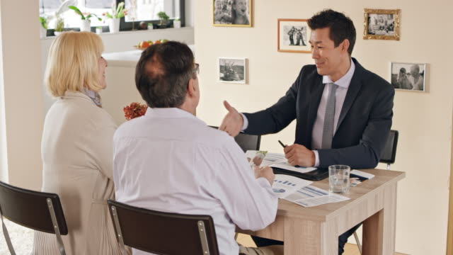 Financial advisor shaking hands with an older couple at a meeting in their home