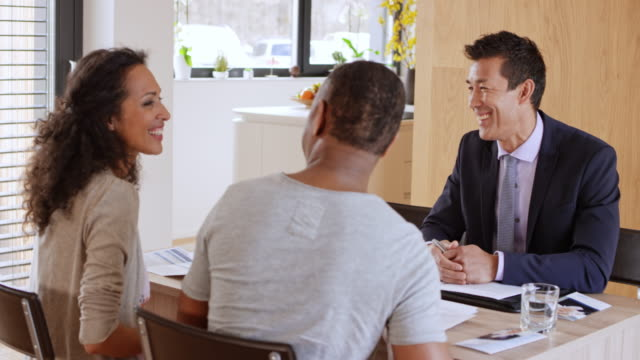 Financial advisor shaking hands with his clients on a meeting in their home