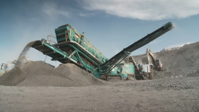 Fine gravel pours from machines at quarry Available in HD.