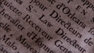 A finger points to a line of text that says Law Directeur on a document. Available in HD.