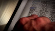 A finger points to a word in a french dictionary and then to a word in an english-french dictionary.