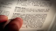 A finger points to words in two french and english dictionaries.