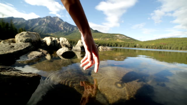 Finger touches surface of mountain lake