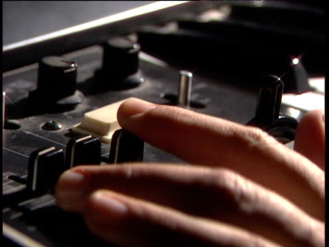 Fingers handling dials and switches including cross fader on recording deck