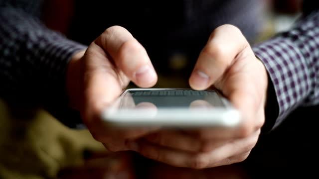 Hände eines jungen Mann SMS auf ein smartphone-Gerät