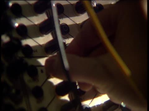 Fingers tweaking knobs on recording equipment