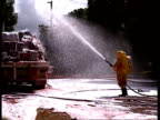 MS Fire fighter in chemical suit hosing down chemicals with foam