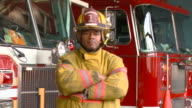 MS PAN PORTRAIT Fire fighter standinging in front of fire engines/ Richmond, Virginia