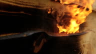 Fire flame burns a wooden surface.