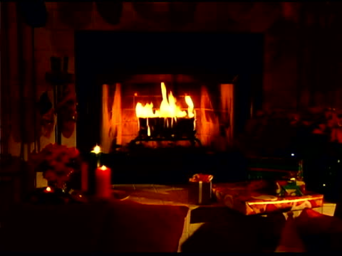 Fire in fireplace in living room with Christmas decorations