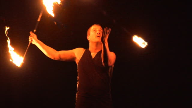 Fire Juggling Spinning with Flames - Performer juggles outdoors night