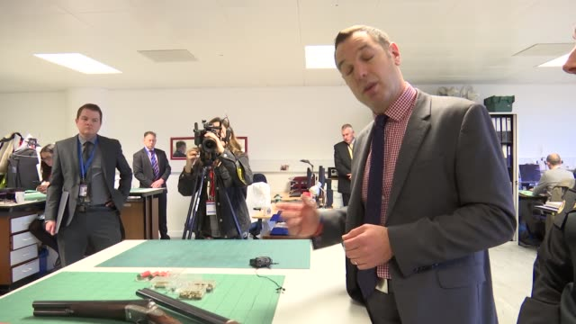 Firearms amnesty / general views guns ENGLAND London INT Guns on table / Police presser describing firearms / bullets / Hand holding bullets and...